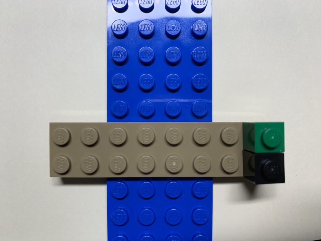 B2樂高畫面 在一格綠色樂高下放上一格黑色樂高